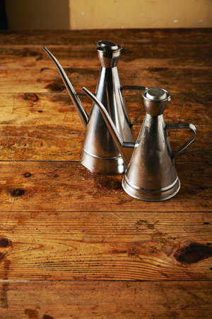 Two similar shaped steel olive oil cruets in a rustic vintage beige toned kitchen on aged wooden table presented close together