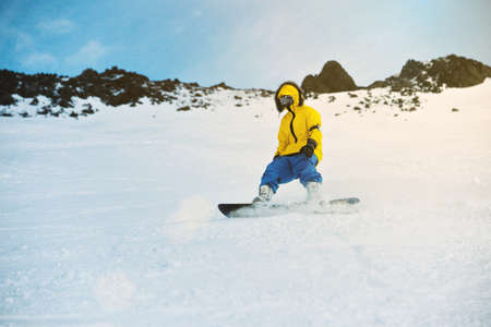 Unrecognizable rider on his snowboard on ski slope in winter mountains is going down or breaking on his backside edge, in ski resort