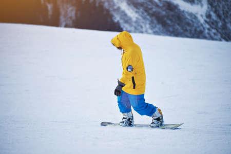pantalones abajo: Snowboarder en la chaqueta amarilla y azul de los pantalones brillantes monta abajo de pendiente en la nieve en el día soleado Winer en la estación de esquí de montaña