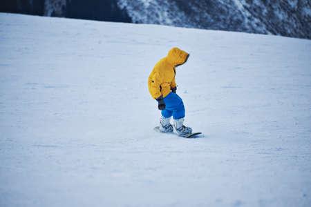 pantalones abajo: Snowboarder en parka amarilla y azul de los pantalones brillantes mira hacia abajo en cuesta de la nieve antes de empezar a montar en el día soleado Winer en la estación de esquí de montaña