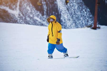 pantalones abajo: Snowboarder en anorak amarillo y azul de los pantalones brillantes está listo para bajar por la pendiente, mirando a la cámara en el día soleado Winer en la estación de esquí de montaña LANG_EVOIMAGES