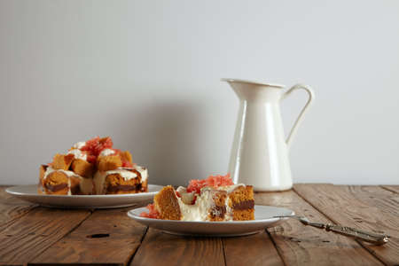 dessert fork: Piece of cake on small ceramic saucer next to silver dessert fork in front of unfocused cake and milk pot on rustic wooden table, isolated on white