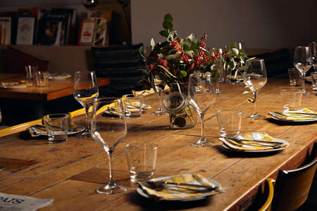 View on beautifully decorated dinner table with transparent wine glasses, table napkins on empty dishes, rustic wooden table and big jar with rowan branches inside, part of daily newspaper seemed on side