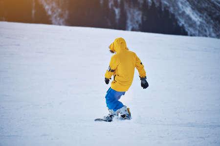 pantalones abajo: Vista posterior del snowboarder en la chaqueta amarilla y azul de los pantalones brillantes monta abajo de pendiente en la nieve en el día soleado Winer en la estación de esquí de montaña