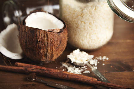 vintage: Close focused opened fresh coconut next to unfocused jar with coconut flakes, cinnamon stick and vintage steel measure spoons with natural brown sugar or grinded coffee, isolated in center on wooden table