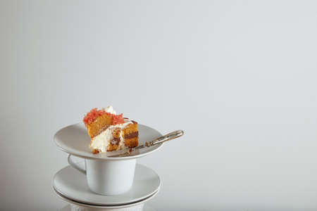 dessert fork: Piece of cake on small ceramic saucer next to silver dessert fork, isolated on white