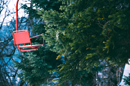 Stylistic photo of old vintage grunged red empty ski lift chair isolated on left, bahinf pine tree branches in winter forest, focus on tree LANG_EVOIMAGES