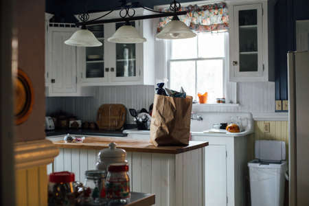 Still life shot of typical provence style american kitchen with white cupboards and vintage elements, paper bag on table with ecologic vegetables