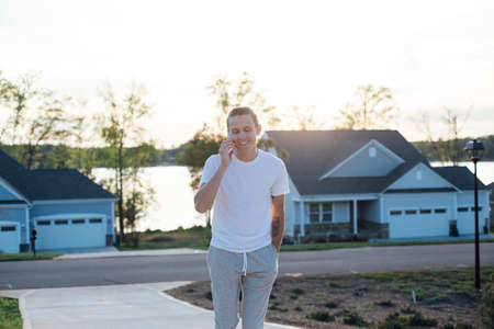 bristles: Attractive millennial man walks on driveway of american house, in his workout clothing, sweatpants and white tshirt talks on smartphone, chats laughs and giggles with friends