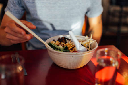 Soft focused shot of vegeterian vegan asian fusion dish, with authentic natural ingridients in fancy downtown cafe restaurant, hipster man eating with chopsticks Stock Photo