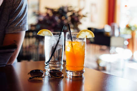 Refreshing glass of ice cold water with cubes, and ice-tea arnold palmer drink with tea and lemonade mixed for hot summer day refreshements with straws