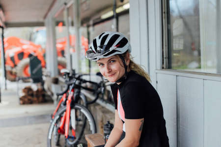 Tired but happy, exhausted after long training ride female rider smiles into camera in her helmet and lycra cycling kit, with professional road bikes in distance Standard-Bild