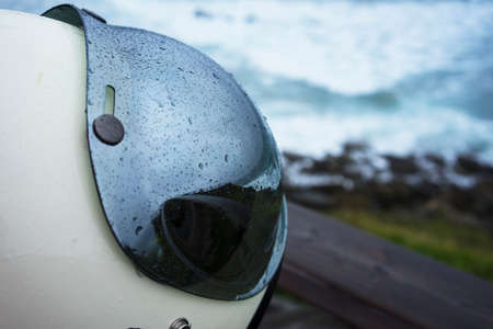 Close up view on white fashionable stylish helmet with raindrops on protective glass on blurred blue ocean background.