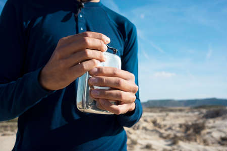 Close up view on man in blue long sleeve t-shirt and his graceful hands opening metal flask with clean fresh water in desert.