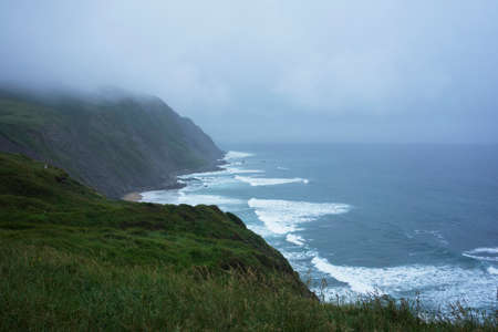 Incredible view on hill with fresh green grass above blue ocean with waves under fog and rain. Horizontal shot. Standard-Bild