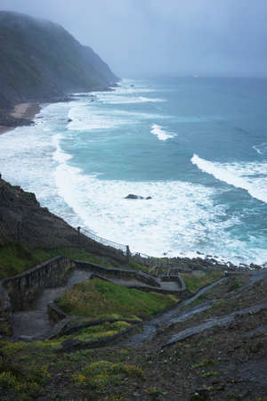 Incredible view on stone stairs leading to blue ocean with waves under fog and rain. Vertical shot.
