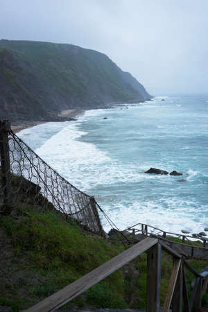 Amazing view on wooden stairs leading to blue choppy ocean in rainy fog day. Vertical shot. Standard-Bild