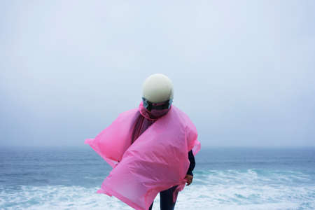 Unrecognizable woman in pink raincoat and white helmet stands above blue ocean in rainy windy fog day.