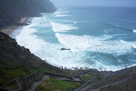 Incredible view on stone stairs leading to blue ocean with waves under fog and rain. Horizontal shot.