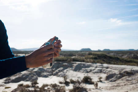 Close up view on man in blue long sleeve t-shirt and his graceful hands opening metal flask with clean fresh water in hot desert.