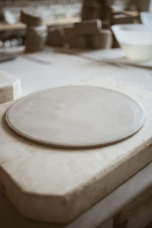Round shape grey raw clay for modeling ceramic plate on big table in workshop