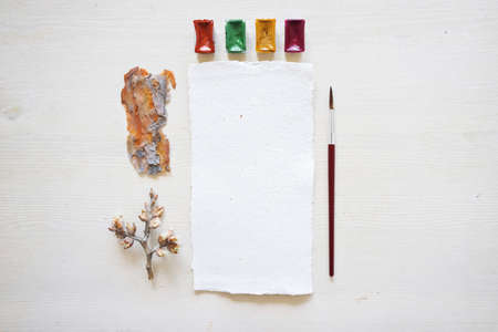 Handcrafted paper with torn edges with watercolor palette, spring twig and bark on wooden table background, top view