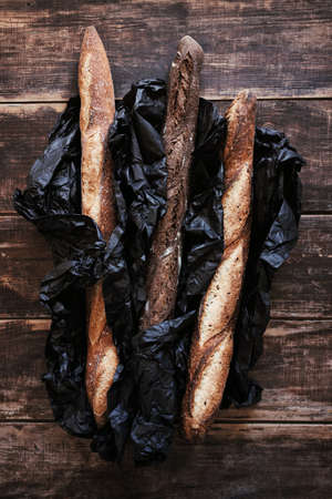 Vertical top view of three artisanal rustic baguettes bread in black craft paper on wooden dark table background.
