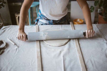 Artist rolls raw clay using big grey rolling pin on table covered with industrial fabric in workshop Standard-Bild