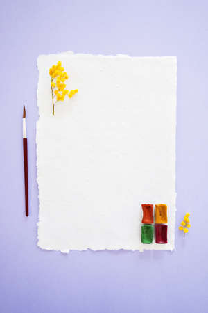 Handcrafted paper with torn edges with watercolor palette, brush for drawing and yellow mimosa flowers on lilac background, top vertical view.