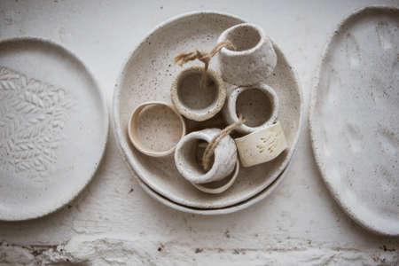 Top view on three grog clay plates with beautiful rustic napkin rings on white background