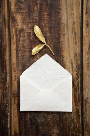 Top view of designer rustic white little handmade envelope with golden leaves on dark wooden table background. Standard-Bild