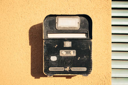 Black cute old fashioned mailbox on yellow wall on house background.