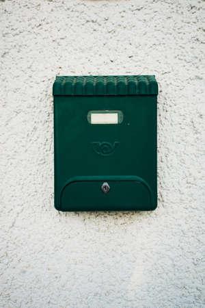 Green beautiful old fashioned mailbox on white wall background. Standard-Bild
