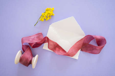 Yellow mimosa flower and handcrafted little white envelope with red ribbon on wooden coil on lilac table, top view Standard-Bild