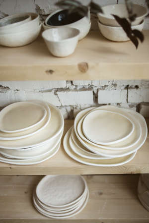 Glazed ceramic beige plates on wooden rustic shelves with white brick wall on background