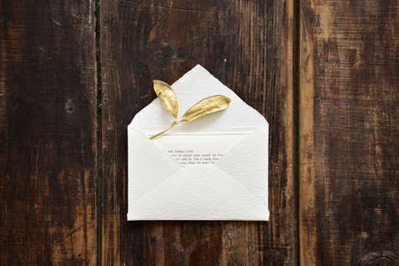 Top view of designer rustic white little envelope with golden leaves and card with text for sending letter on dark wooden table background.