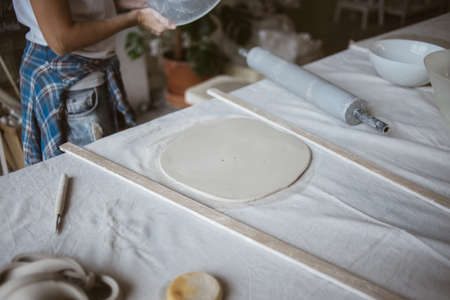 Rolled out piece of clay ready for modeling ceramic plate on big table with industrial fabric in workshop Standard-Bild