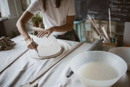 Sculptor cuts grey raw clay round plastic bowl for modeling ceramic plate on big table with industrial fabric in workshop
