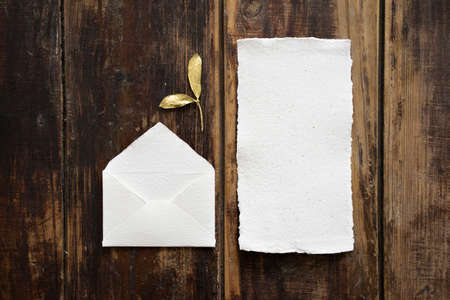 Top view of designer rustic white little envelope with golden leaves and empty handmade card for writing letter of congratulation on dark wooden table background. Standard-Bild