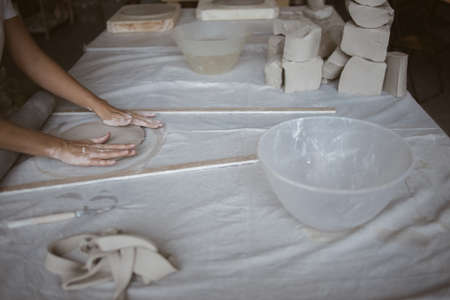 Artist modeling raw clay using hands on table covered with industrial fabric in workshop Standard-Bild