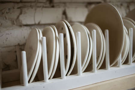 Ceramic white plates in rustic wooden dish holder on shelf with white brick wall in background Standard-Bild