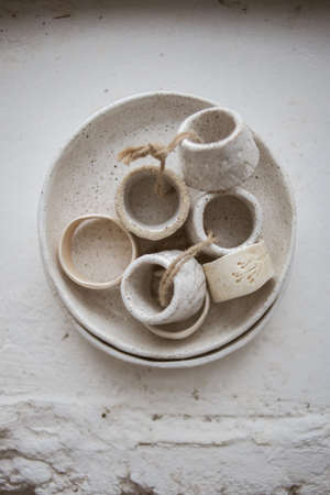 Top view on grog clay plate with beautiful rustic napkin rings on white background Standard-Bild