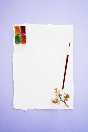 Handcrafted paper with torn edges with watercolor palette, brush for drawing and spring twig on lilac background, top vertical view.