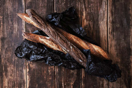 Horizontal top view of three artisanal rustic baguettes bread in black craft paper on wooden dark table background.