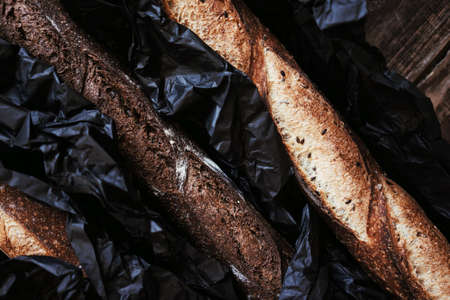 Close up view of three artisanal rustic baguette bread in black craft paper on wooden dark table background.