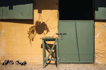 Empty stable for horses with green door and yellow wall on ranch Standard-Bild