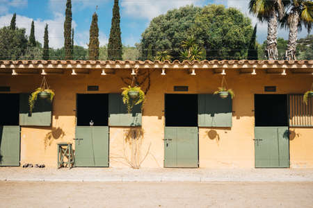 Empty stables for horses with yellow wall and green doors on ranch Standard-Bild