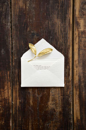 Top vertical view of designer rustic white little envelope with golden leaves and card with text for sending letter on dark wooden table background.