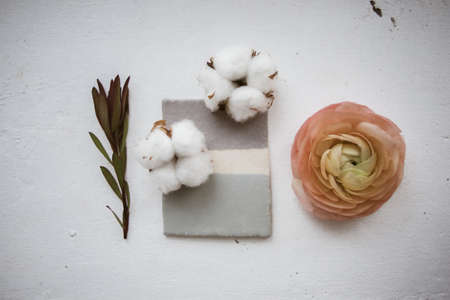 Ceramic glazed tile with flowers of cotton, ranunculus on white texture of windowsill