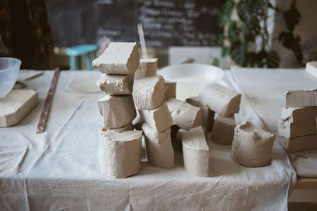 Pieces of grey raw clay for modeling ceramic ware on big table with industrial fabric in workshop
